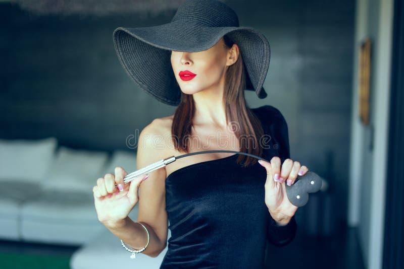 Fatale dominant passionné de femme dans le chapeau avec le portrait de fouet photo stock