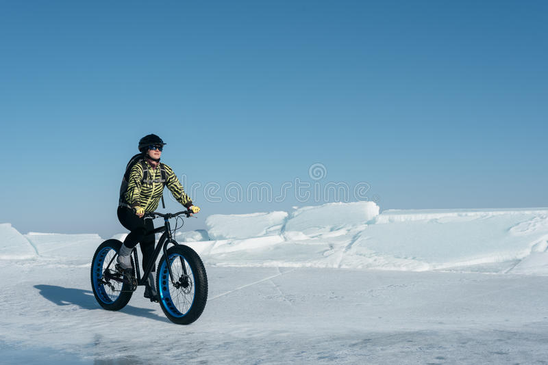 Fatbike (fat bike or fat-tire bike). Fatbike (also called fat bike or fat-tire bike) - Cycling on large wheels. Extreme girl riding a bike on snow melted ice stock images