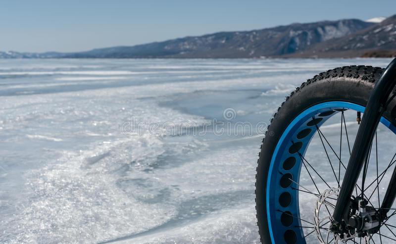 Fatbike fat bike or fat-tire bike. Fatbike also called fat bike or fat-tire bike - Cycling on large wheels. Bike standing on the ice of Lake Baikal, near frozen royalty free stock images