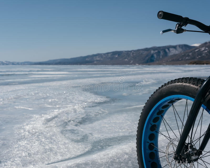Fatbike fat bike or fat-tire bike. Fatbike also called fat bike or fat-tire bike - Cycling on large wheels. Bike standing on the ice of Lake Baikal, near frozen royalty free stock photography