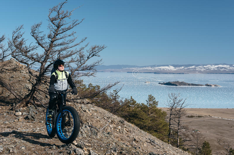 Fatbike (fat bike or fat-tire bike). Fatbike (also called fat bike or fat-tire bike) - Cycling on large wheels. Teen riding a bike on a hill in the mountains royalty free stock photography