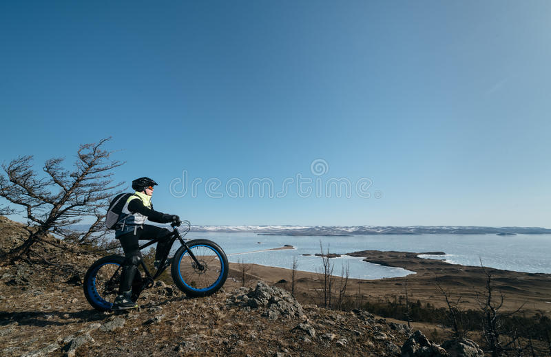 Fatbike (fat bike or fat-tire bike). Fatbike (also called fat bike or fat-tire bike) - Cycling on large wheels. Teen riding a bike on a hill in the mountains stock photography