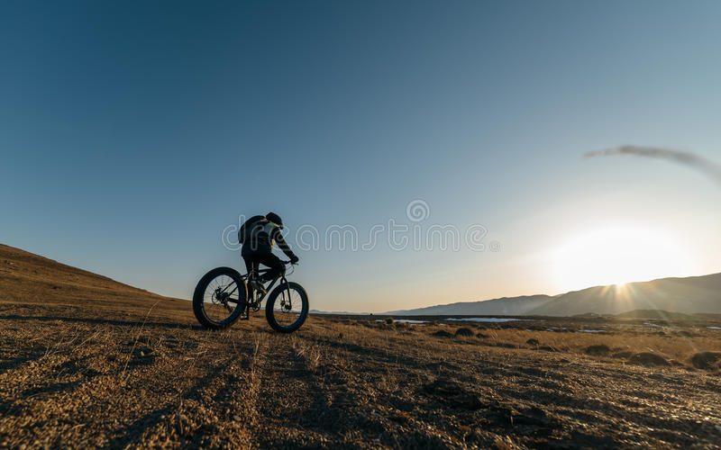 Fatbike fat bike or fat-tire bike. Fatbike also called fat bike or fat-tire bike - Cycling on large wheels. Traveller athlete cyclist rides with mountains in the stock photography