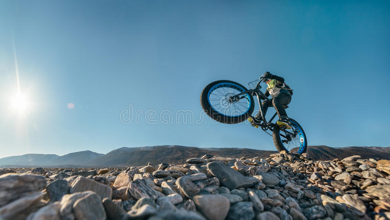 Fatbike fat bike or fat-tire bike. Fatbike also called fat bike or fat-tire bike - Cycling on large wheels. Traveller athlete jumps on the bike on the rocky stock image