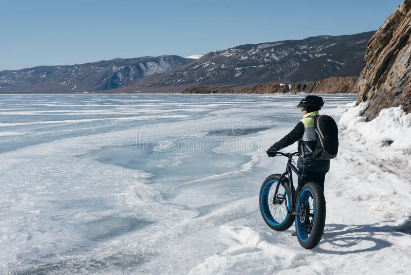 Fatbike fat bike or fat-tire bike. Fatbike also called fat bike or fat-tire bike - Cycling on large wheels. Traveller athlete standing on the ice of Lake Baikal stock photo