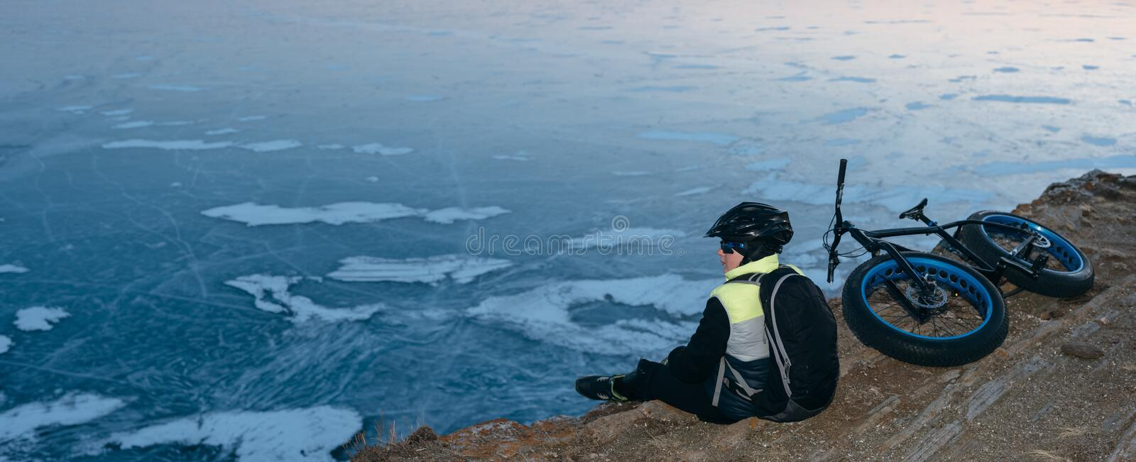 Fatbike fat bike or fat-tire bike. Fatbike also called fat bike or fat-tire bike - Cycling on large wheels. Traveller cyclist sits on a hillside. He is resting royalty free stock photo