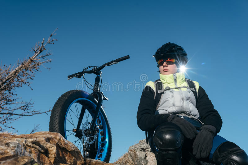 Fatbike fat bike or fat-tire bike. Fatbike also called fat bike or fat-tire bike - Cycling on large wheels. Traveller cyclist sits on top of the mountain. He is stock images