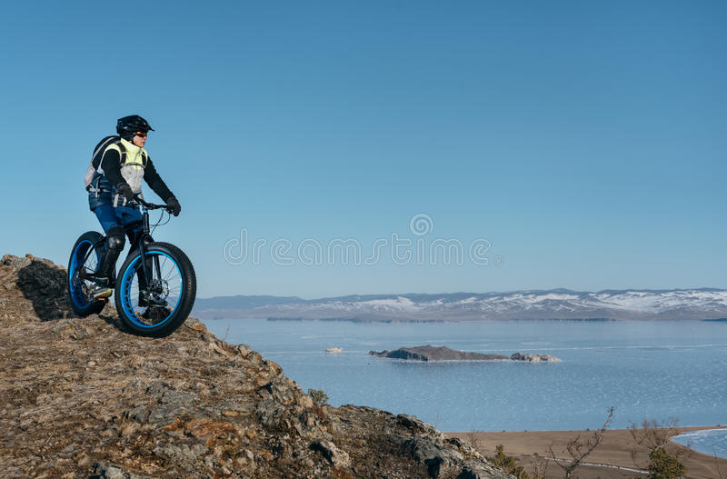 Fatbike fat bike or fat-tire bike. Fatbike also called fat bike or fat-tire bike - Cycling on large wheels. Traveller cyclist stands on the top of the mountain royalty free stock photo