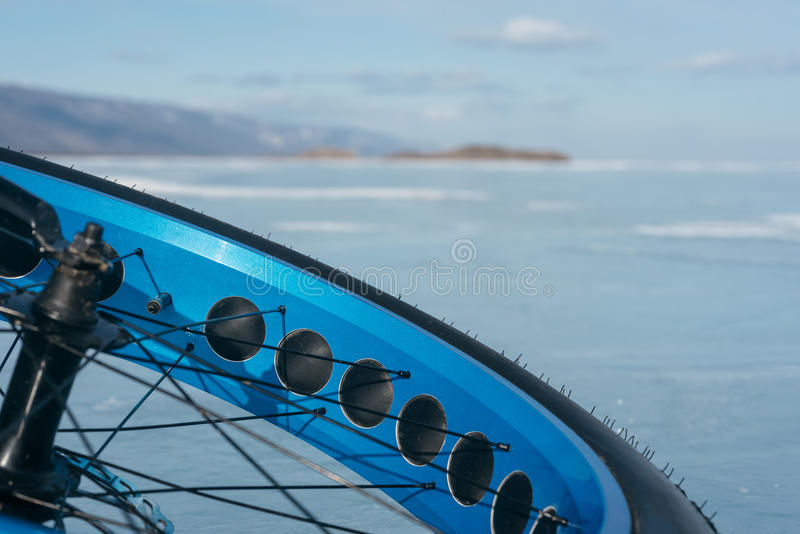 Fatbike. Fat tire bike. Fatbike also called fat bike or fat-tire bike - Cycling on large tire wheels. Cyclist goes to his bike on the frozen lake stock photography