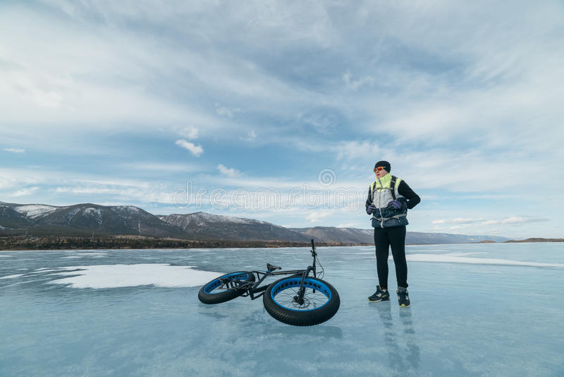 Fatbike. Fat tire bike. Fatbike also called fat bike or fat-tire bike - Cycling on large tire wheels. Cyclist goes to his bike on the frozen lake royalty free stock photography