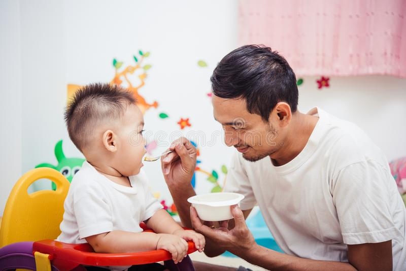 Father acting Mom feeding his son baby 1 year old on chair stock image