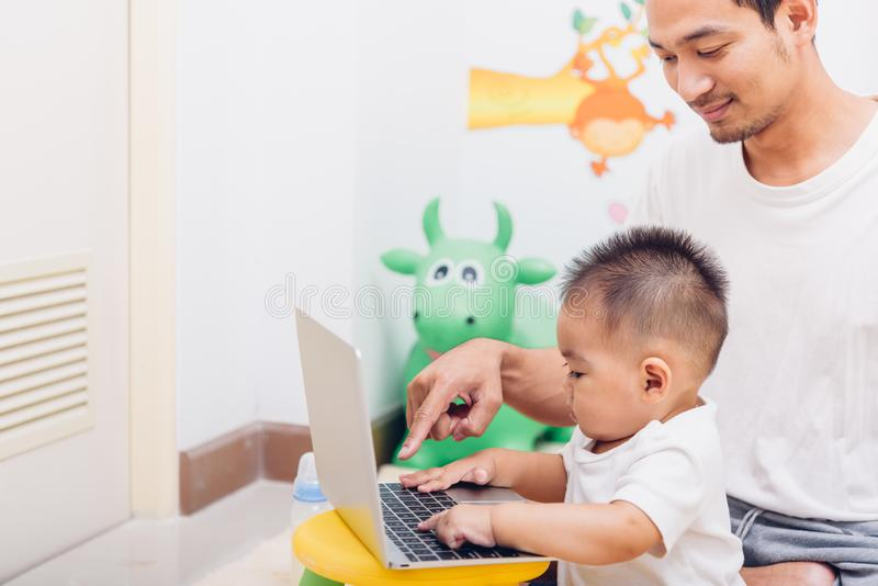 Father acting Mom feeding milk his son baby 1 year old while working on laptop computer stock photo