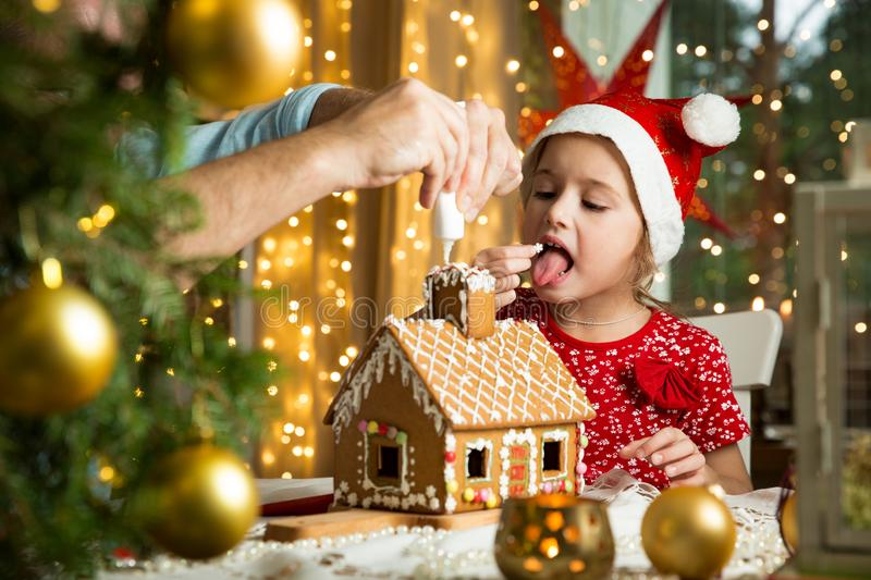 Father and adorable daughter in red hat building Christmas gingerbread house. Father and adorable daughter in red hat building gingerbread house together royalty free stock photo
