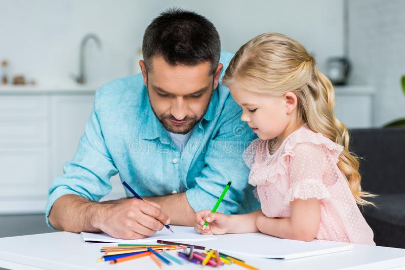 Father and adorable little daughter drawing with colored pencils together at home royalty free stock photography