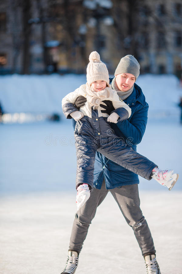 Father and adorable little girl having fun on skating rink outdoors. Young dad and adorable little girl have fun on skating rink stock photos