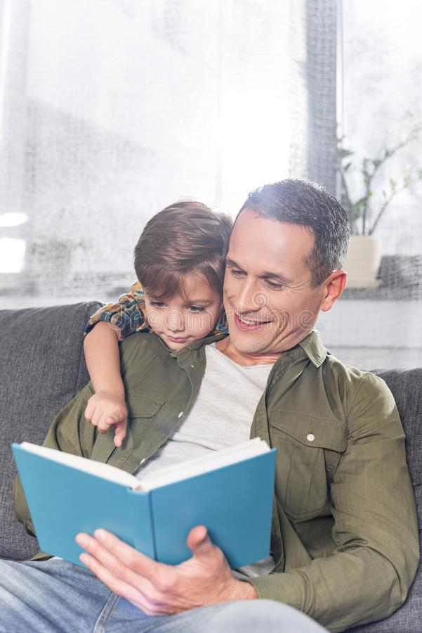 father and adorable son reading book together while sitting stock photos