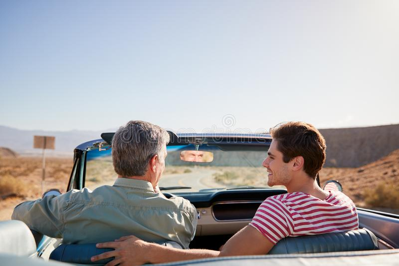 Father and adult son on road trip in open top car, back view royalty free stock photo