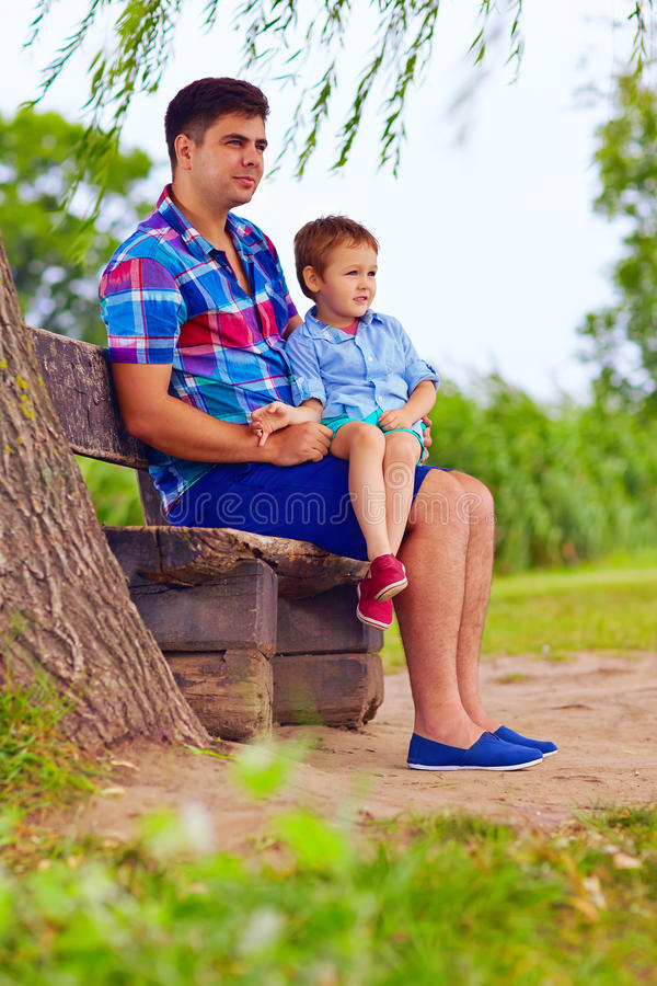 Free Father And Son Sitting On The Bench Under Willow Tree Royalty Free Stock Photography - 43341157