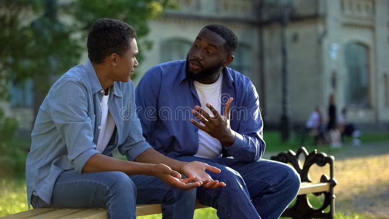 Father arguing teenage son sitting on campus bench, puberty age difficulties stock photos
