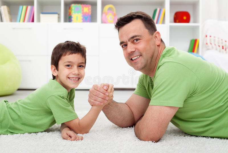 Father arm wrestling with his boy. Happy family time together stock photography