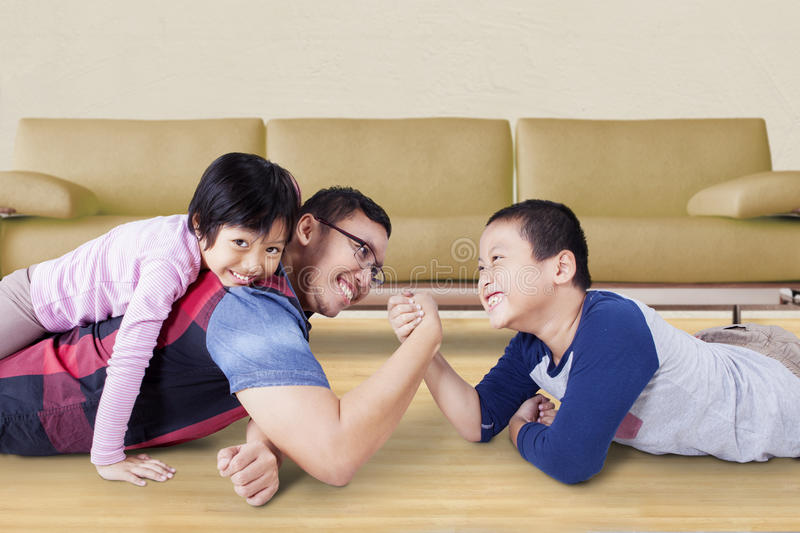 Father arm wrestling with his boy. Image of young father playing with his kids and arm wrestling with his son at home stock photos