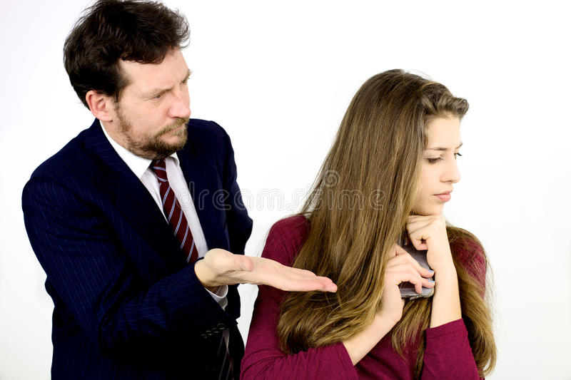 Father asking daughter to give him the cell phone. Father punishing daughter isolated in studio stock image