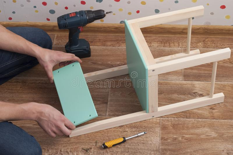Father assembles a chair for children royalty free stock photography