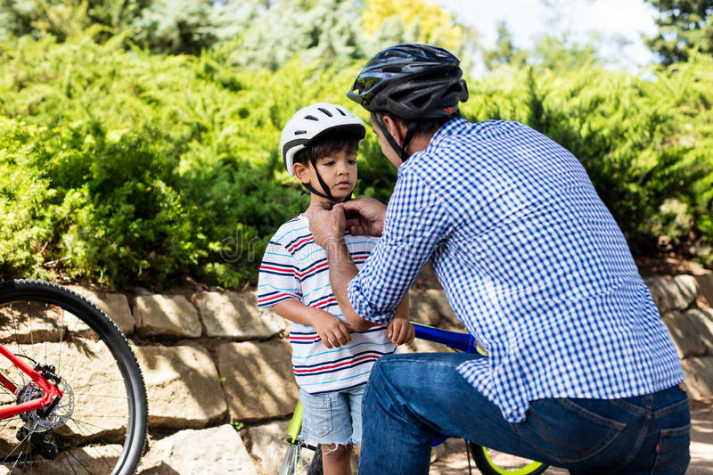 Father assisting son in wearing bicycle helmet in park. On a sunny day royalty free stock photos