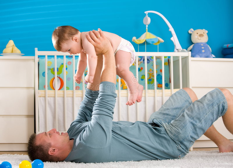Father and baby. Father lying on back and lifting baby boy ( 1 year old ) at home in children's room stock photo