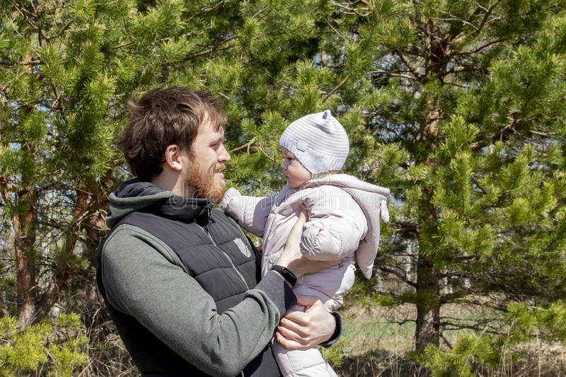 A father with a baby in his arms is walking in the park. A young man with a beard holds a child girl 9 months stock photography