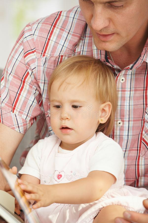 Father and baby reading book stock photography