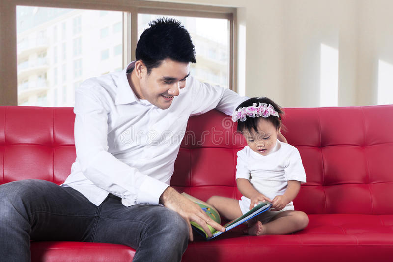 Father and baby reading story book together. Lovely father reading story book with his baby at home stock photos