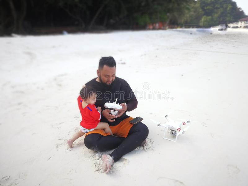 Father and the baby sitting while using drone. stock photo