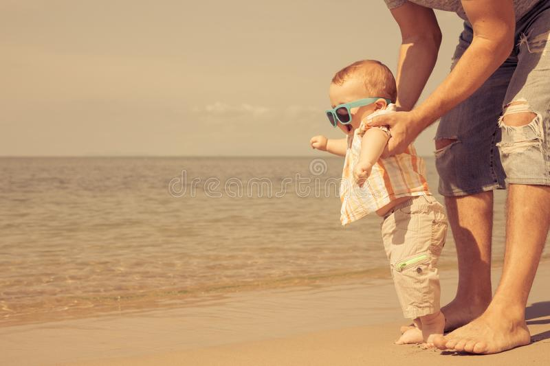Father and baby son playing on the beach at the day time. stock photo