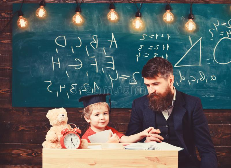 Father with beard, teacher teaches son, little boy. Teacher and pupil in mortarboard, chalkboard on background stock photo