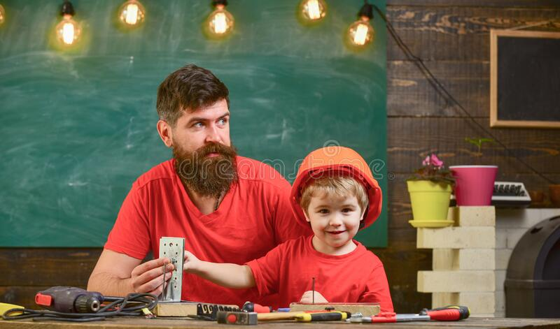 Father with beard teaching little son to use tools in classroom, chalkboard on background. Boy, child busy in protective royalty free stock photo