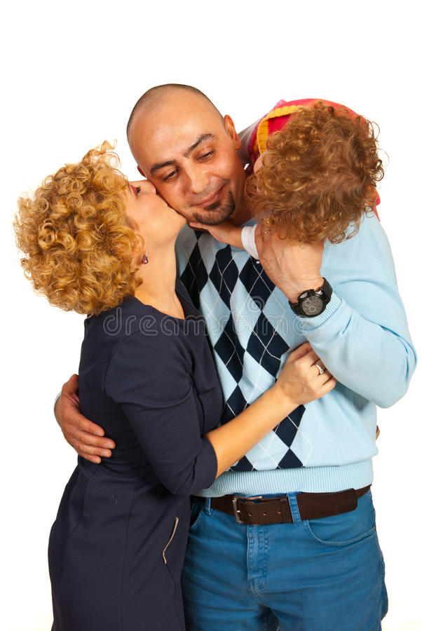 Father being kissed by wife and daughter royalty free stock photo