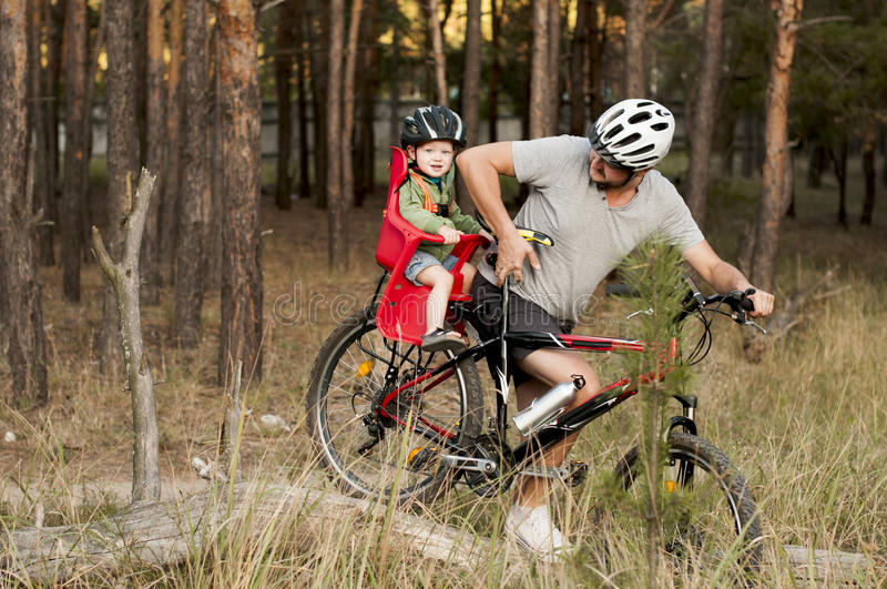 Father on bicycle with little son climbs over a log stock photo