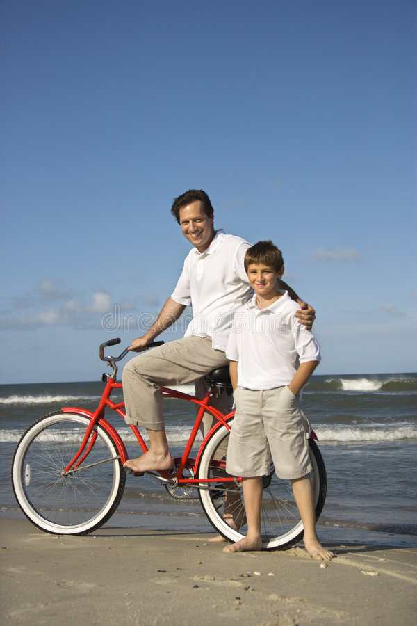 Father on bike with son on beach. royalty free stock photos