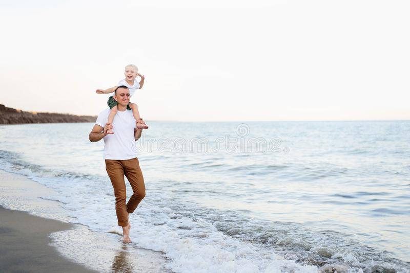 Father with a blond son on her shoulders are walking along the seashore. Family vacation stock photos