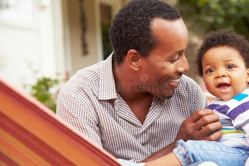 Father bonding with young son sitting in a hammock royalty free stock images