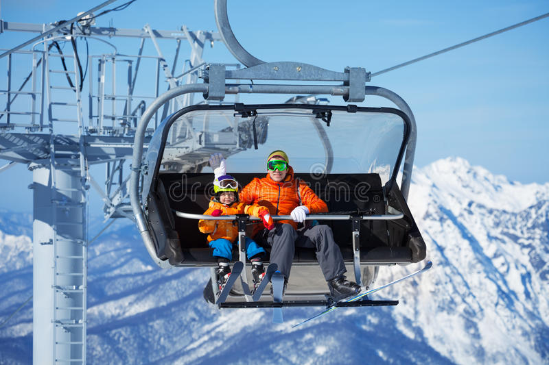 Father and boy sit in ski lift over mountains. Father and little boy skiers sitting on the chair on ropeway lift with high mountain with snow on background royalty free stock photography