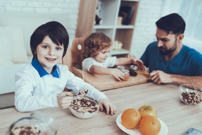 Father is Feeding His Sons a Breakfast royalty free stock photography