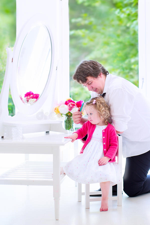Father brushing hair of his charming daughter stock photos