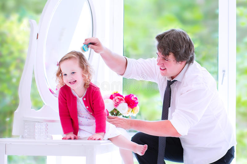 Father brushing hair of his sweet daughter stock photo