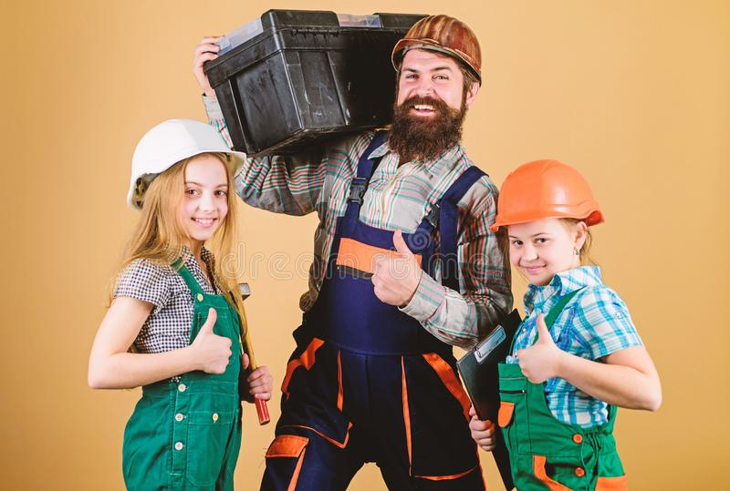 Father builder kids girls. Informal education. Fathers day. Sisters help father builder. Our dad has skillful fingers stock photo
