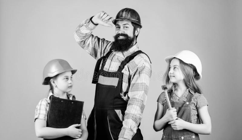 Father builder and kids girls repair home. Teach daughter. Informal education. Fathers day. Sisters help father builder royalty free stock image