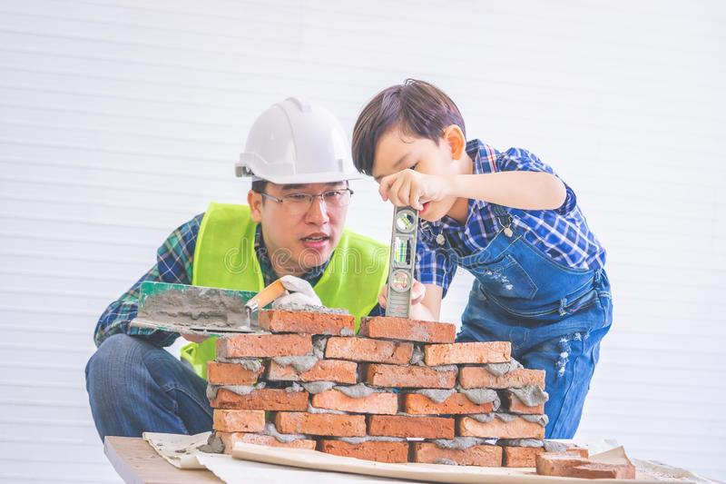 Father builder teaching his son to lay the brick wall for future career and education for family and parenting concept stock photography