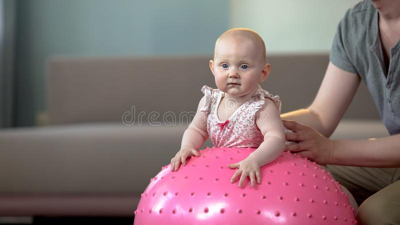 Father carefully holding baby girl on big ball, fitness exercises for infant stock image