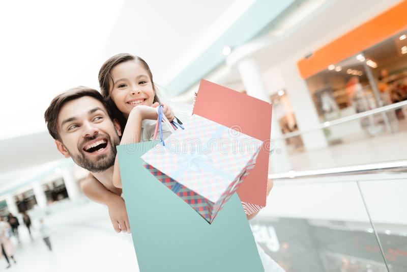 Father carries daughter on back in shopping mall. Girl and man are excited. royalty free stock photography